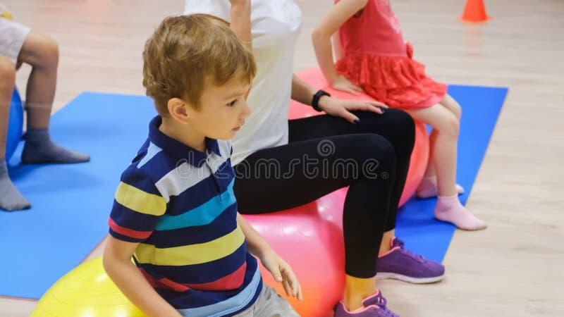 Groep Gelukkige sportieve kinderen` s oefening met bal, geschiktheidsgymnastiek royalty-vrije stock afbeeldingen
