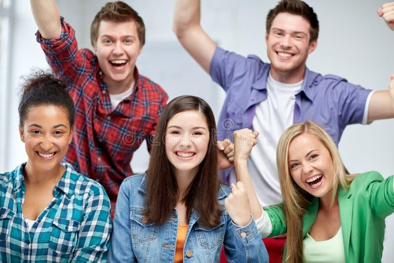 Groep gelukkige studenten die triomfgebaar maken stock fotografie
