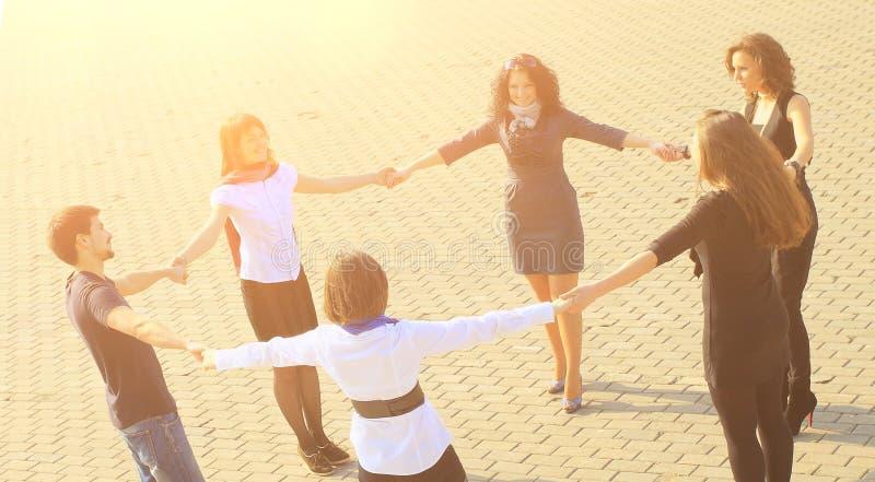 Groep gelukkige studenten handen houden die zich bevindt in een cirkel royalty-vrije stock foto