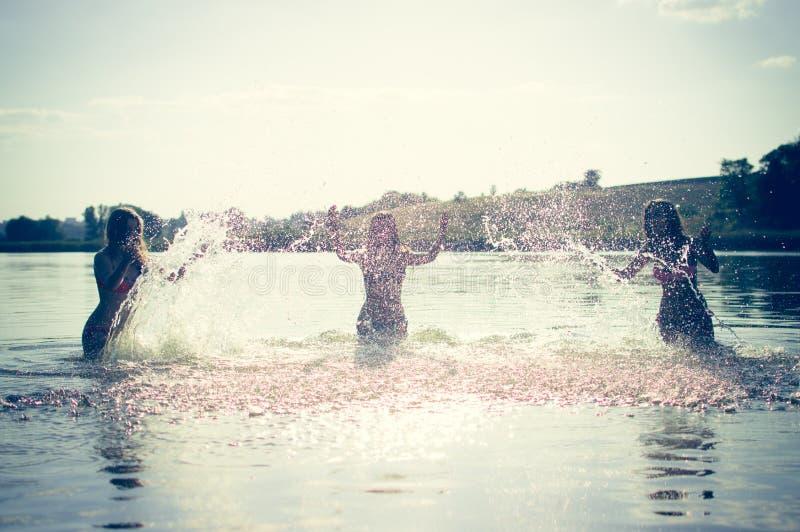 Groep gelukkige tienermeisjes die in water spelen stock afbeelding