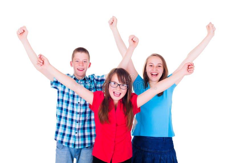 Groep gelukkige tieners die handen opheffen stock fotografie