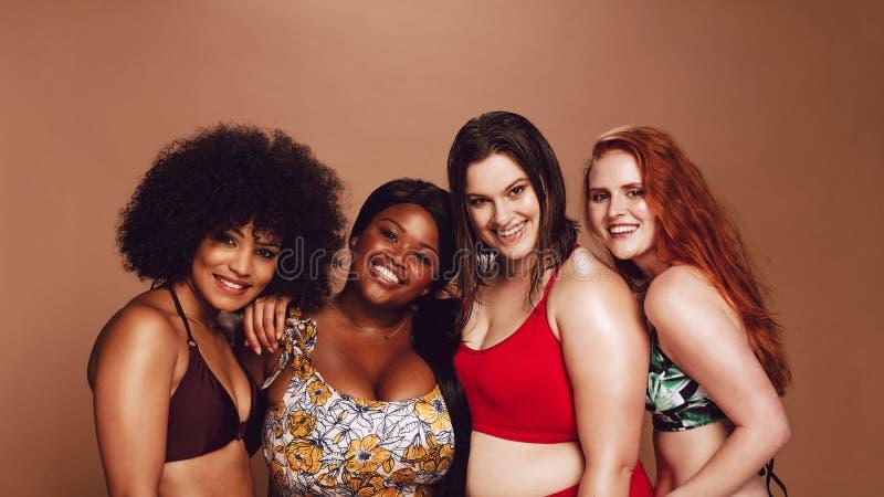 Groep gelukkige verschillende groottevrouwen in bikinis royalty-vrije stock afbeeldingen