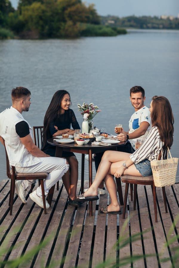 Groep gelukkige vrienden die aan het hebben van diner zich samen verzamelen royalty-vrije stock foto