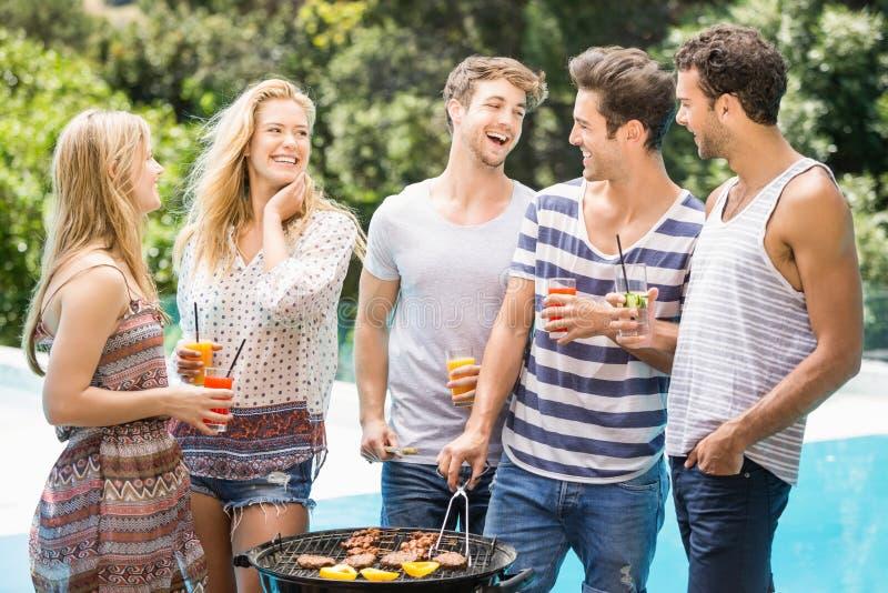 Groep gelukkige vrienden die barbecue voorbereiden dichtbij pool stock foto