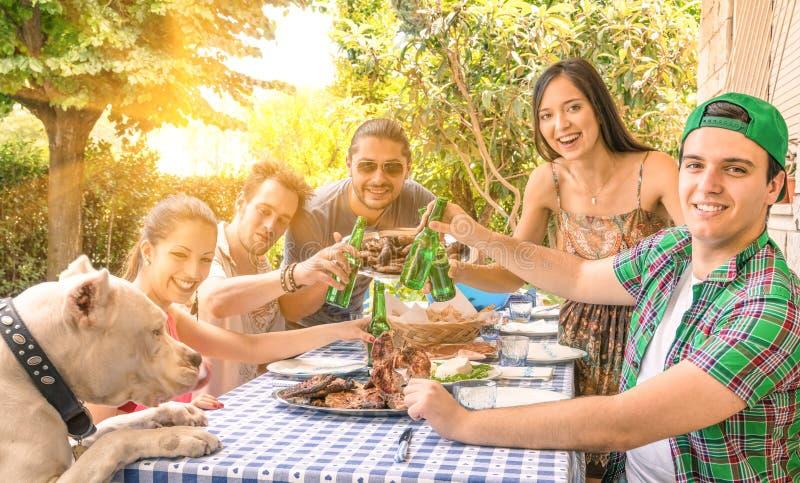 Groep gelukkige vrienden die bij tuin eten stock afbeeldingen
