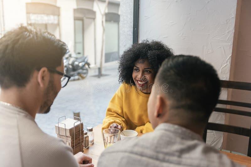 Groep gelukkige vrienden die in de koffiewinkel babbelen stock afbeeldingen