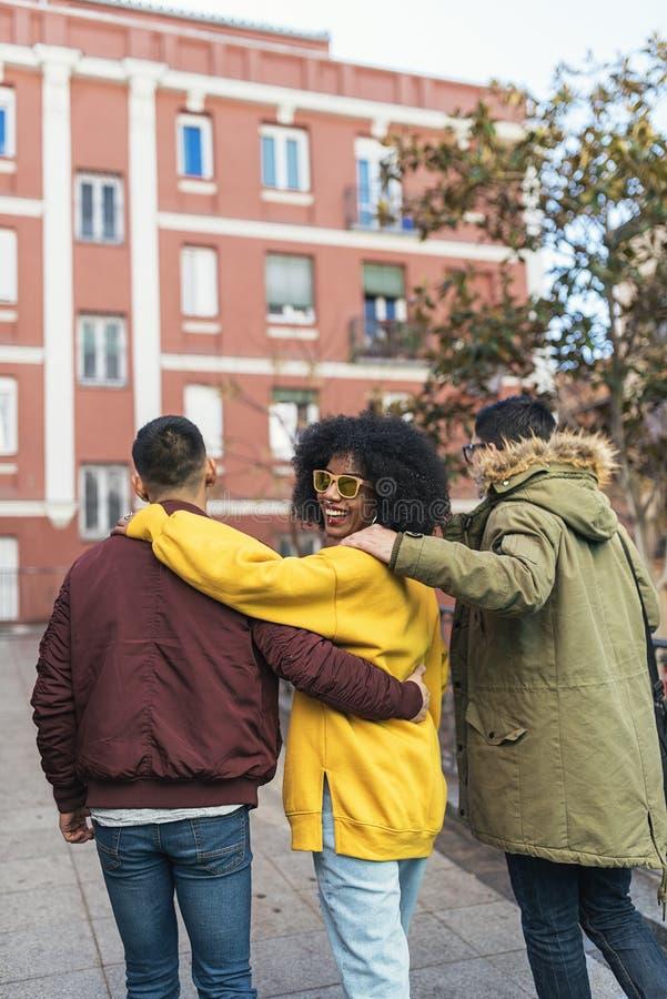 Groep gelukkige vrienden die in de straat lopen Het concept van de vriendschap royalty-vrije stock afbeelding