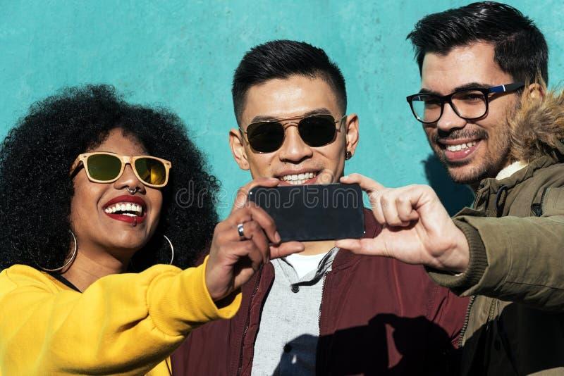 Groep gelukkige vrienden die een selfie in de straat nemen stock afbeeldingen