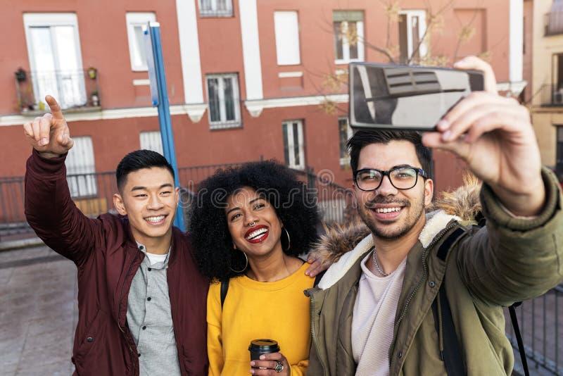 Groep gelukkige vrienden die een selfie in de straat nemen royalty-vrije stock afbeeldingen