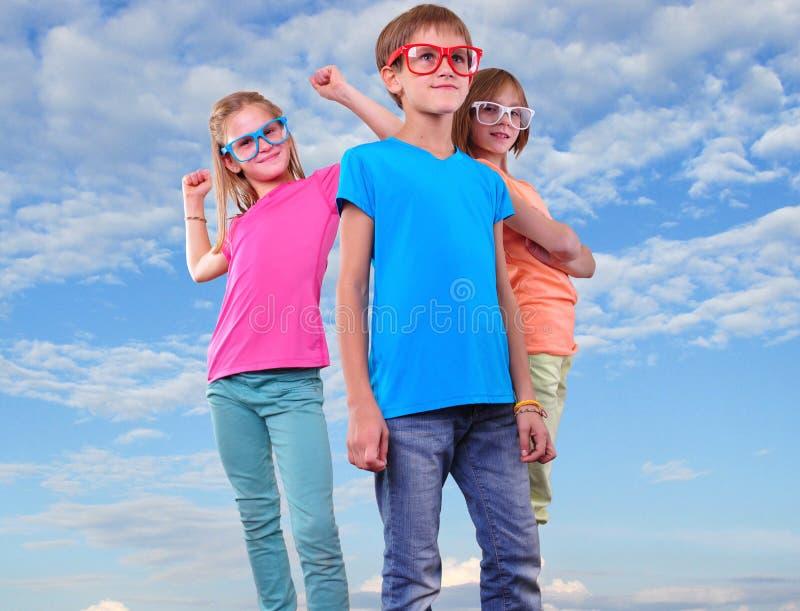 Groep gelukkige vrienden die eyeglassesahainst blauwe hemel dragen stock foto