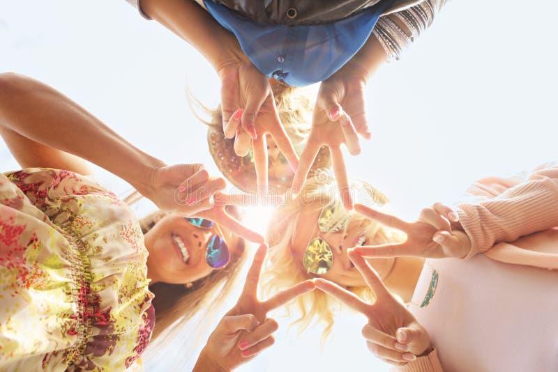 Groep gelukkige vrienden die tekens tonen stock foto