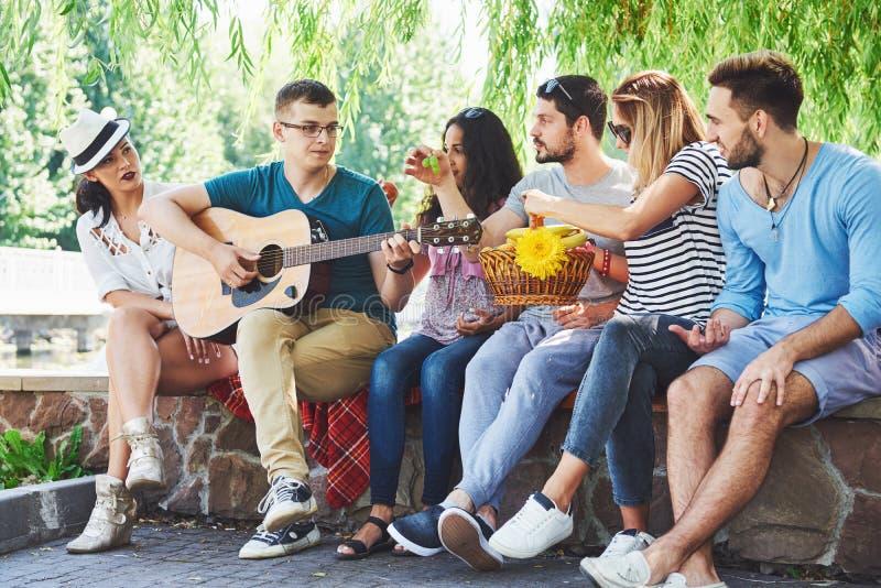 Groep gelukkige vrienden met gitaar Terwijl één van hen gitaar speelt en anderen geven hem een ronde van applaus stock afbeelding