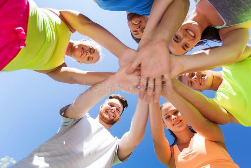 Groep gelukkige vrienden met handen op bovenkant in openlucht royalty-vrije stock fotografie