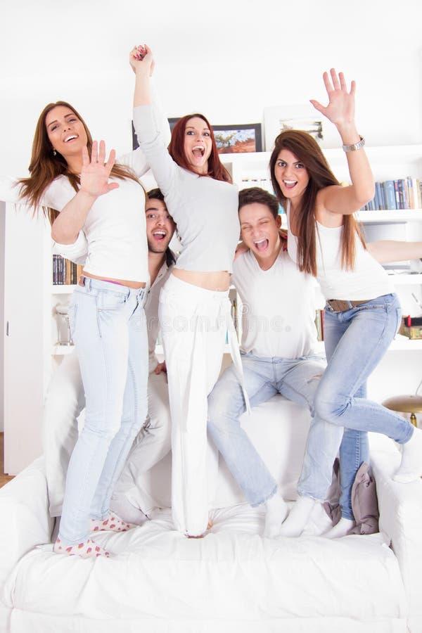 Groep gelukkige vrienden op bank in huis het glimlachen stock foto