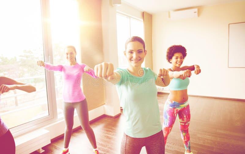Groep gelukkige vrouwen die in gymnastiek uitwerken stock fotografie
