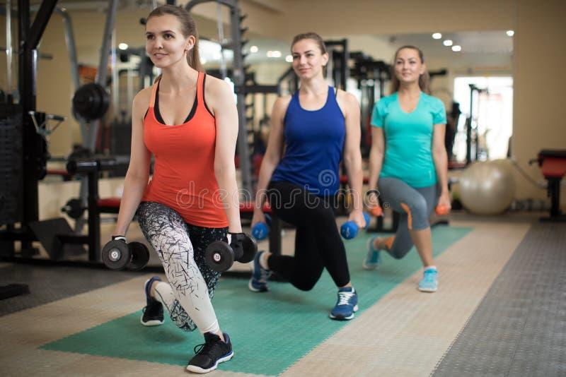 Groep gelukkige vrouwen met domoren die spieren in gymnastiek buigen Concept sport, fitness, gezondheid en levensstijl royalty-vrije stock foto