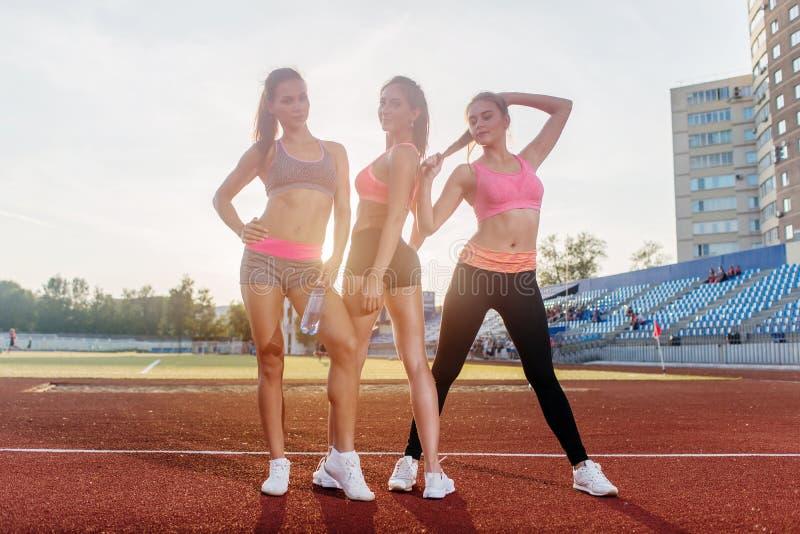 Groep geschikte jonge sportvrouwen die zich bij atletiek stadion en het stellen bevinden royalty-vrije stock foto's