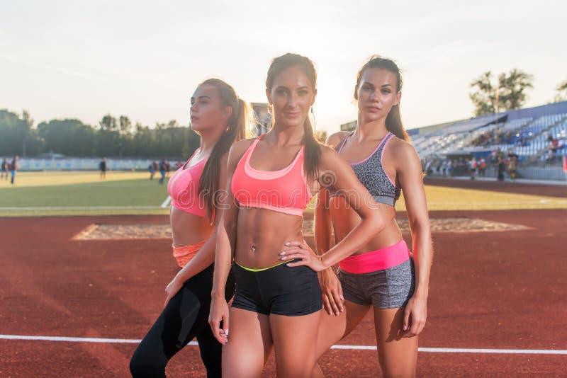 Groep geschikte jonge sportvrouwen die zich bij atletiek stadion en het stellen bevinden stock foto