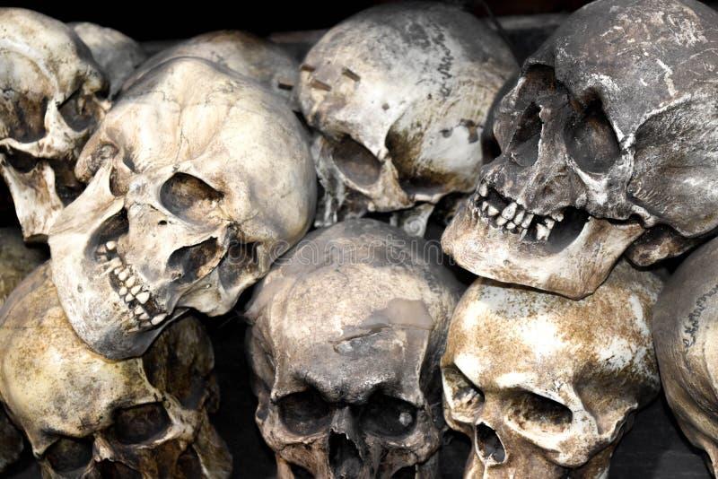 Groep gestapelde schedels van dood mensenbeeldhouwwerk stock afbeeldingen