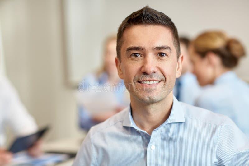 Groep glimlachend zakenlui die in bureau samenkomen royalty-vrije stock afbeelding