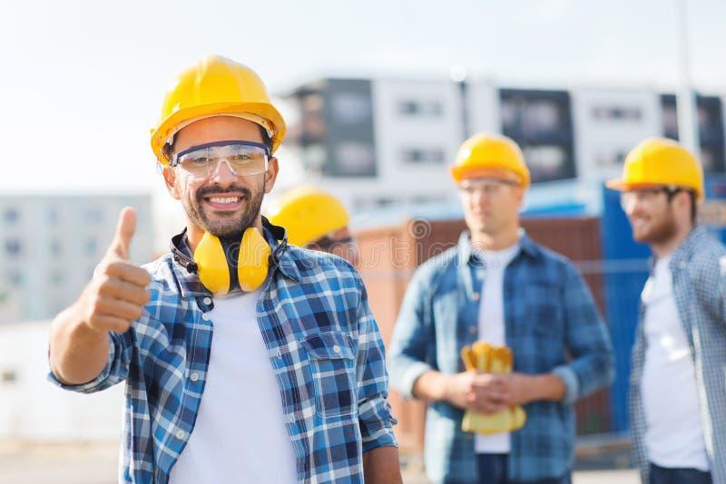 Groep glimlachende bouwers in bouwvakkers in openlucht stock foto