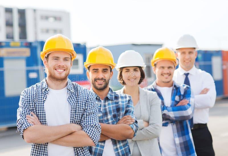 Groep glimlachende bouwers in bouwvakkers in openlucht stock fotografie