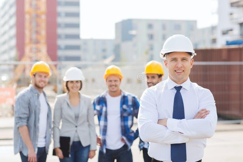 Groep glimlachende bouwers in bouwvakkers in openlucht stock foto's