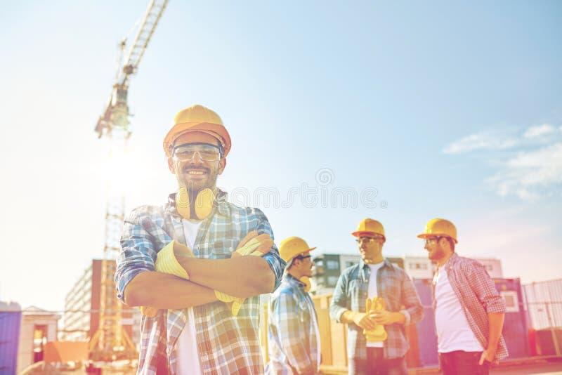 Groep glimlachende bouwers in bouwvakkers in openlucht royalty-vrije stock afbeeldingen
