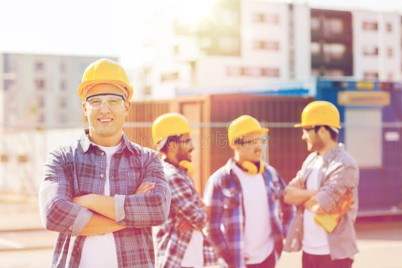 Groep glimlachende bouwers in bouwvakkers in openlucht royalty-vrije stock foto's