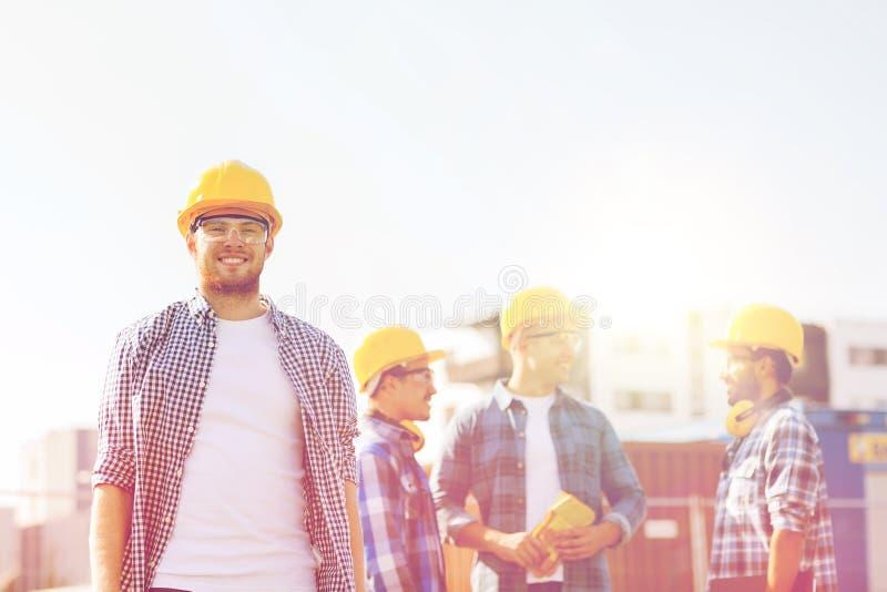 Groep glimlachende bouwers in bouwvakkers in openlucht stock afbeeldingen