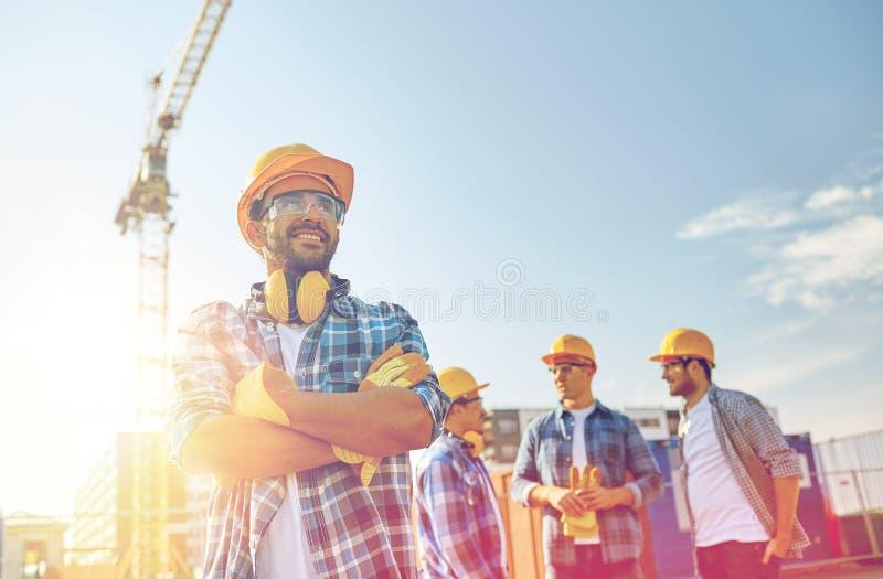 Groep glimlachende bouwers in bouwvakkers in openlucht stock afbeelding
