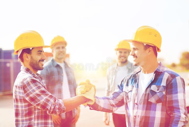 Groep glimlachende bouwers die handen in openlucht schudden royalty-vrije stock afbeelding