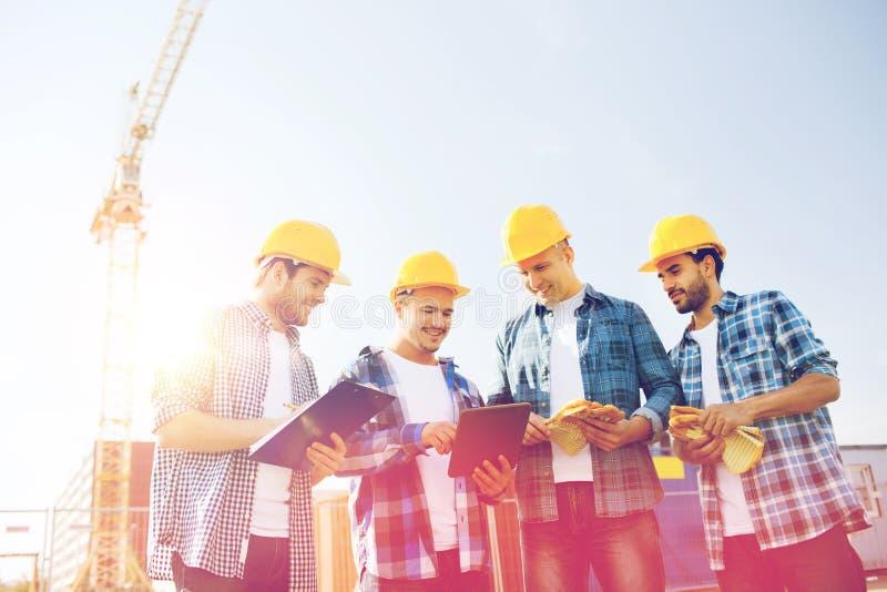 Groep glimlachende bouwers met tabletpc in openlucht royalty-vrije stock afbeeldingen