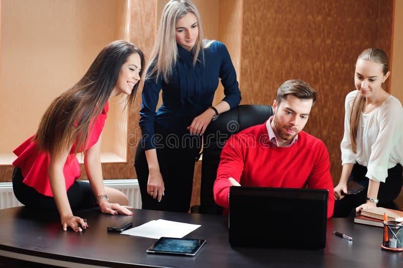 Groep glimlachende geïnspireerde jonge bedrijfsmensen die in bureau samenwerken stock foto
