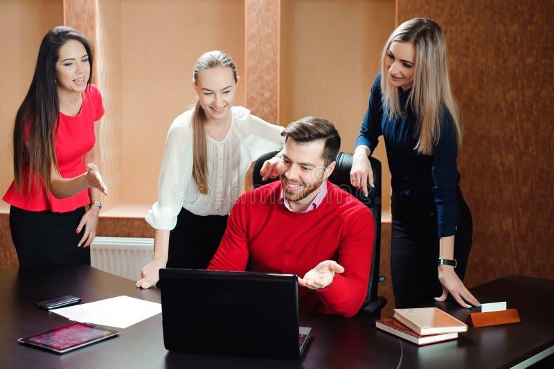 Groep glimlachende geïnspireerde jonge bedrijfsmensen die in bureau samenwerken royalty-vrije stock afbeelding