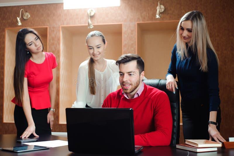 Groep glimlachende geïnspireerde jonge bedrijfsmensen die in bureau samenwerken stock afbeeldingen