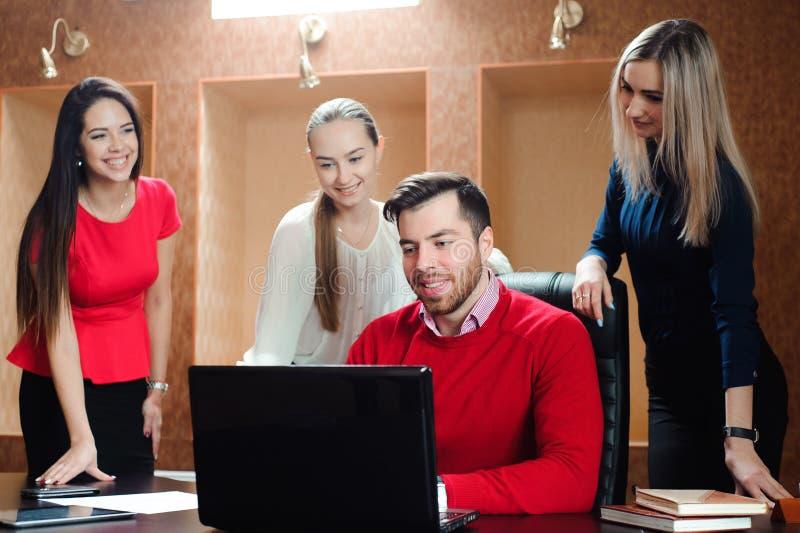 Groep glimlachende geïnspireerde jonge bedrijfsmensen die in bureau samenwerken stock foto's