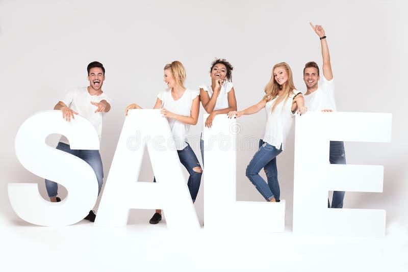 Groep glimlachende jongeren die met verkoopbrieven stellen royalty-vrije stock afbeelding