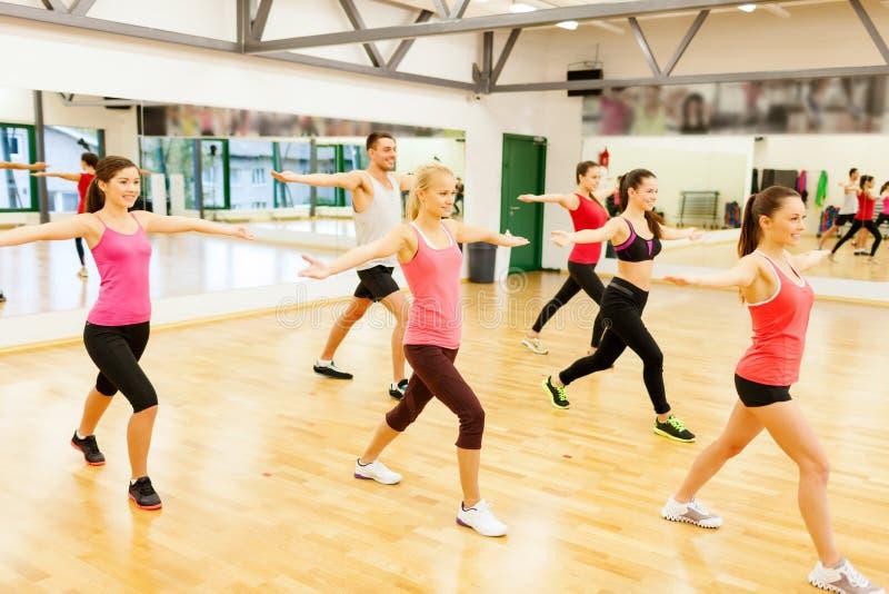 Groep glimlachende mensen die in de gymnastiek uitoefenen royalty-vrije stock afbeeldingen