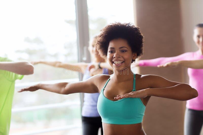 Groep glimlachende mensen die in gymnastiek of studio dansen stock fotografie
