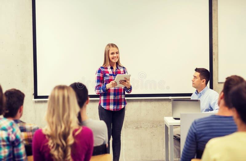 Groep glimlachende studenten en leraar in klaslokaal stock fotografie