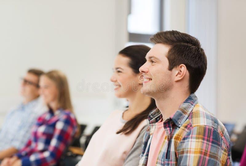 Groep glimlachende studenten in lezingszaal royalty-vrije stock fotografie