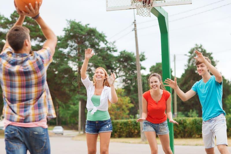 Groep glimlachende tieners die basketbal spelen stock fotografie