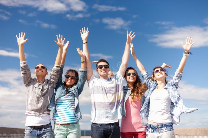 Groep glimlachende tieners die handen omhoog houden stock afbeeldingen