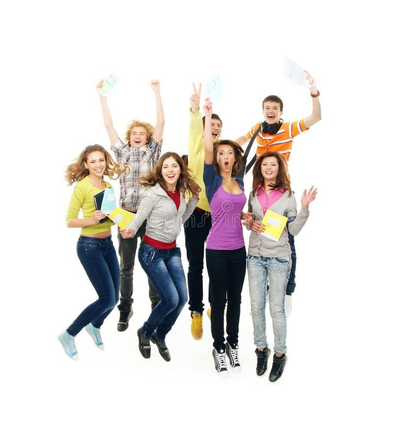 Groep glimlachende tieners die samen springen stock fotografie