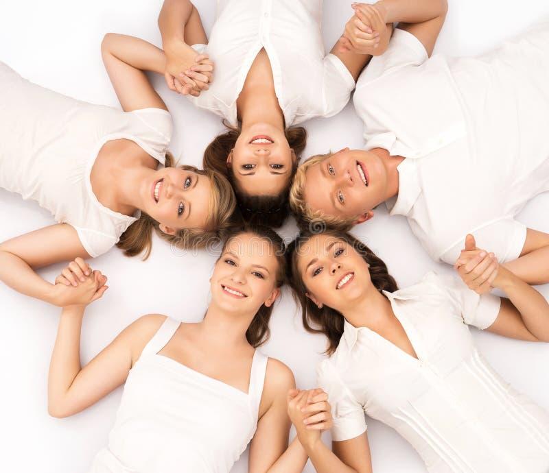 Groep glimlachende tienervrienden die camera bekijken royalty-vrije stock foto