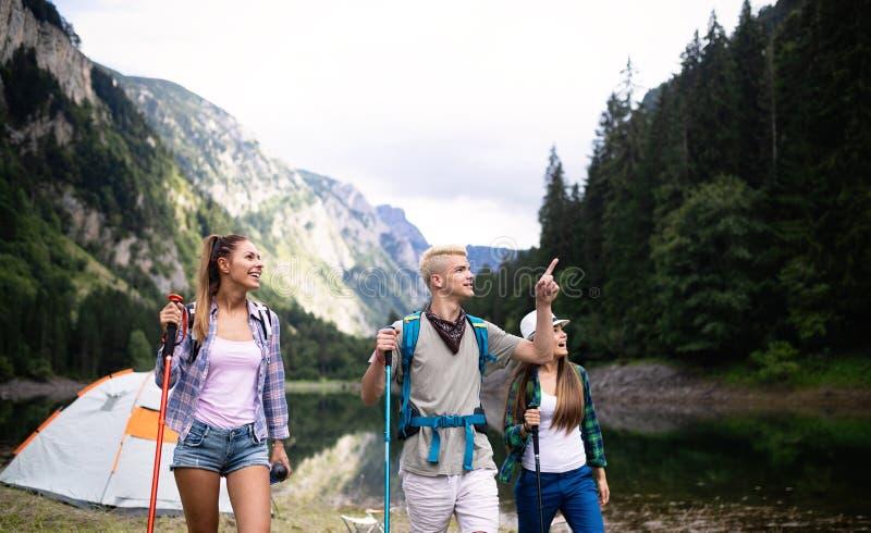 Groep glimlachende vrienden die met rugzakken in openlucht wandelen Reis, toerisme, stijging en mensenconcept stock foto's