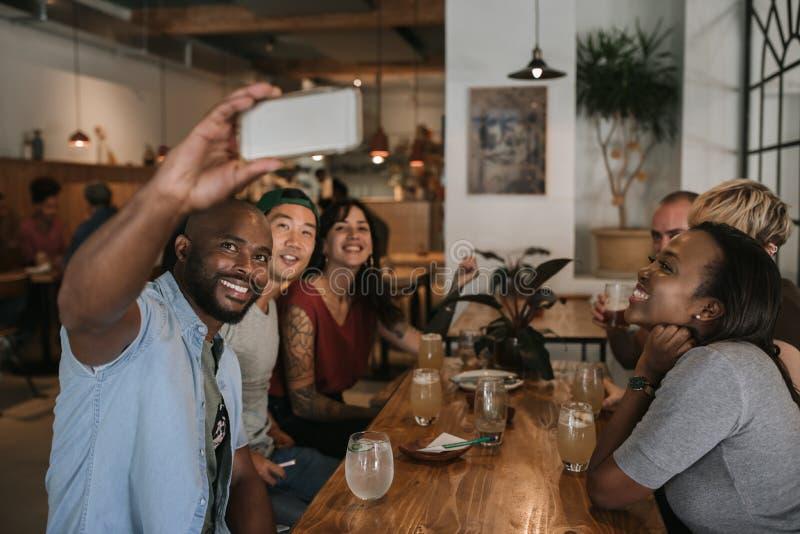 Groep glimlachende vrienden die selfies samen in een bar nemen royalty-vrije stock afbeelding