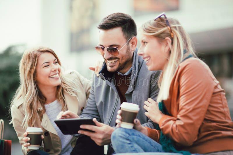 Groep glimlachende vrienden met digitale tablet stock foto