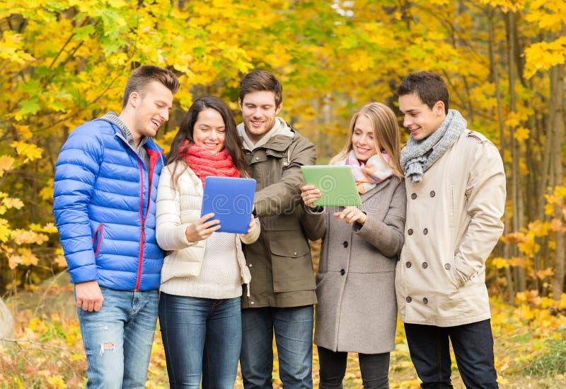 Groep glimlachende vrienden met tabletten in park stock foto